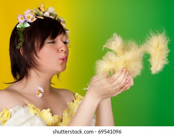 Springtime girl with butterfly and flower hair blowing easter feathers