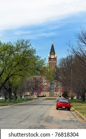 Springtime green and red bud trees grace the avenue leading up to Friends University in Wichita, Kansas.