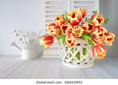 Springtime greeting card design with bunch of red tulips and spring decorations on light wooden background