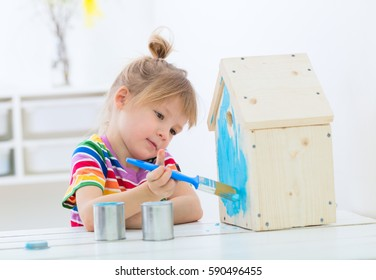 springtime indoors kids activity, girl painting new nest house with bright colors