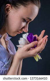 Springtime mood. Pensive attractive girl with the first spring flowers