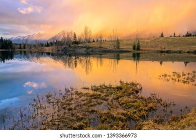 Springtime Mountain Landscape and Dramatic Sunset Colors at Quarry Lake above City of Canmore in Alberta Foothills of Canadian Rockies near Banff National Park