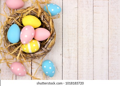 Springtime nest with pink, yellow and blue painted Easter Eggs. Side border against a rustic white wood background.