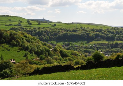 springtime pennine countryside in calderdale west yorkshire with typical hillside fields, woodland, houses and stoodley pike monument in the distance
