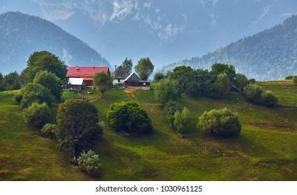 Springtime rural landscape with Romanian village on a green hill near Piatra Craiului Mountain range, in Magura, Brasov county, Transylvania, Romania.