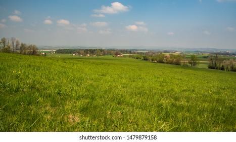 springtime rural scenery with meadows, fields, forest and dispersed settlement from road above Komorni Lhotka village bellow Prasiva hill in Moravskoslezske Beskydy mountains in Czech republic