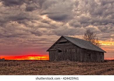 The springtime sun sets behind the old barn house on the fields just reviving of the harsh winter of the Northern Finland.