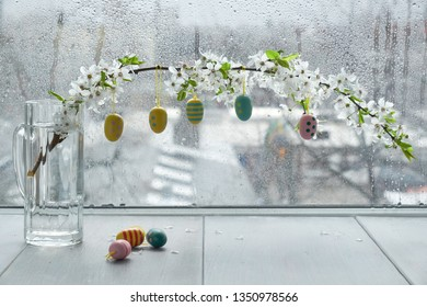Springtime table with Easter eggs hanging from twig covered with white flowers by the window on a rainy day