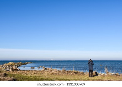 Springtime view with a photographer by the coast at the swedish island Oland