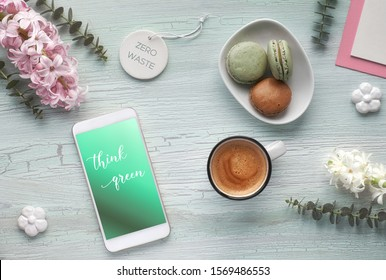 Springtime zero waste flat lay with coffe, macarons, pearl hyacinth flowers, eucalyptus, mobile phone and gift postcards. Concept top view of change in one's lifestyle.