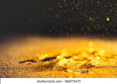 Sprinkle gold dust on a black background with copy space