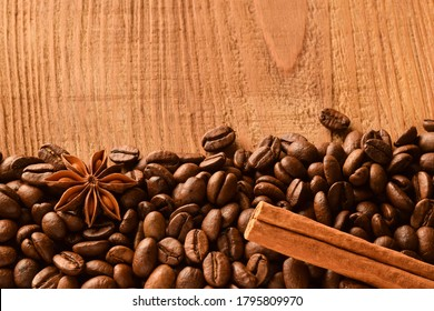 Sprinkled coffee beans at the bottom of the photo, as well as anise and cinnamon. Top photo of empty wood background
