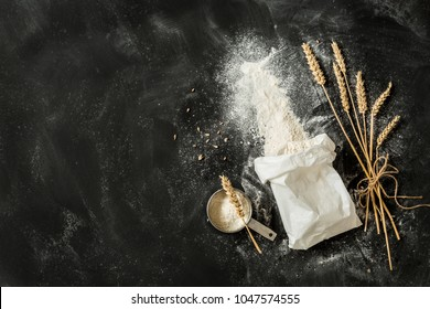Sprinkled flour coming out from the white paper bag, measuring cup and ears of wheat. Captured from above (top view, flat lay) on black chalkboard background. Layout with free text (copy) space.