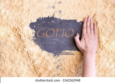 Sprinkled Gofio, Canarian flour made from different roasted grains, and word GOFIO in Spanish on the middle.