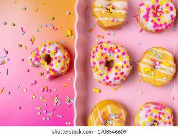 Sprinkled mini donuts on a pink serving tray on a colorful background