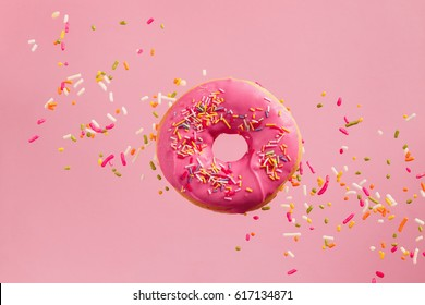 Sprinkled Pink Donut. Frosted sprinkled donut on pink background.