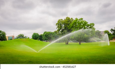 Sprinkler of automatic watering over green grass in the parks.