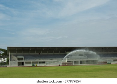 Sprinkler spray water to grass field in football stadium.