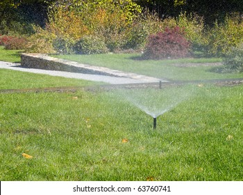 Sprinkler Watering lawn on a sunny autumn day