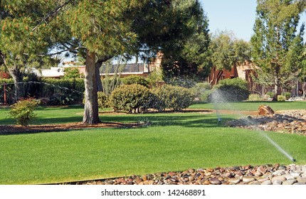 Sprinklers water the grass in park