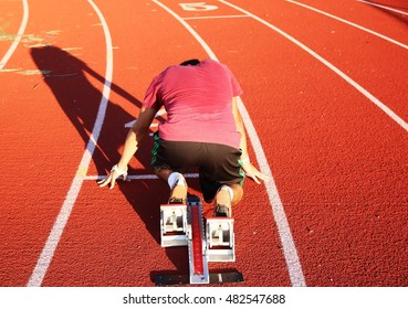A sprinter from behind, in the blocks on a red track