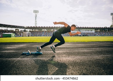 Sprinter leaving starting blocks on the running track