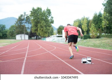 Sprinter Man Running on Red Tracks Lanes in Track and Field Stadium in High Speed Top View