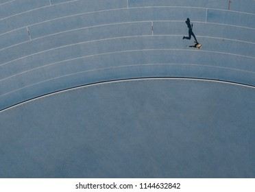 Sprinter running on athletic track. Top view of a sprinter running on race track in a stadium with shadow falling on the side.