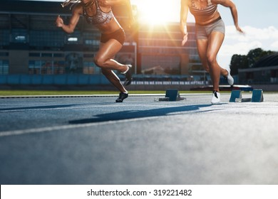 Sprinters starts out of the blocks on athletics racetrack with bright sunlight. Low section shot of female athletes starting a race in stadium with sunflare.