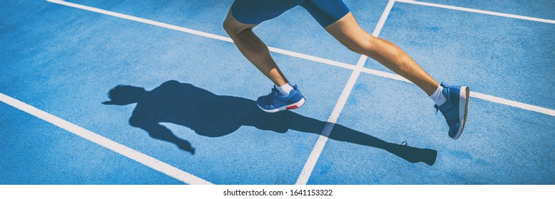 Sprinting man runner sprinter athlete running shoes and legs on track and field lane run race competing fast panoramic banner background.