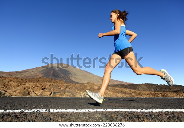 Sprinting running woman - female runner training outdoors jogging on mountain road in amazing landscape nature. Fit beautiful fitness model working out for marathon outside in summer.