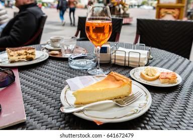 Spritz Aperol drink with traditional snacks cicchetti, ricotta cheesecake and tiramisu in Italian cafe. Traditioanal italian dessert. Image with small depth of field