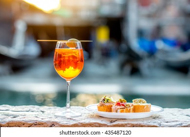 Spritz Aperol drink with venetian traditional snacks cicchetti on the water chanal background in Venice. Traditioanal italian aperitif. Image with small depth of field