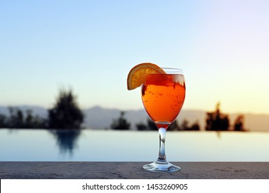 Spritz Veneziano, an Italian wine-based cocktail drink, served on a summer evening at the pool, copy space in the clear sky, selected focus