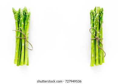 Sprouts of fresh asparagus on white background top view copyspace