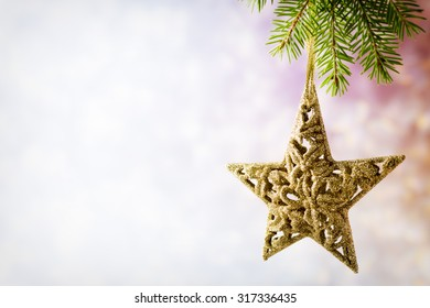 Spruce branch with Christmas decorations on a gray background.
