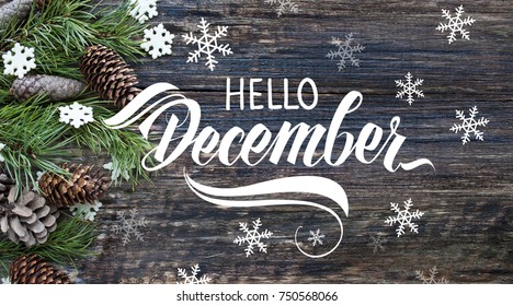 """Spruce branches, cones and snowflakes on old wooden rustic background. Nature december background with hand lettering """"Hello December""""."""