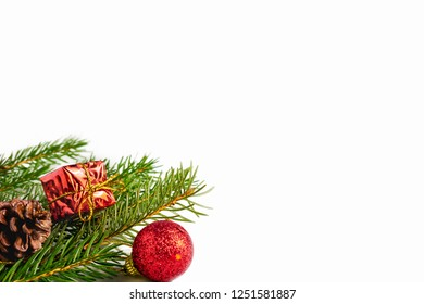 Spruce, fir tree branches with Christmas decorations on white background with copy space