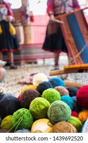 Spun and colored yarn in foreground with Quechuan women in background demonstrating process of creating clothing