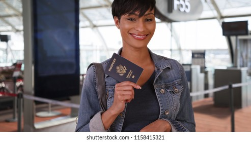 Spunky African woman at airport poses confidently with passport