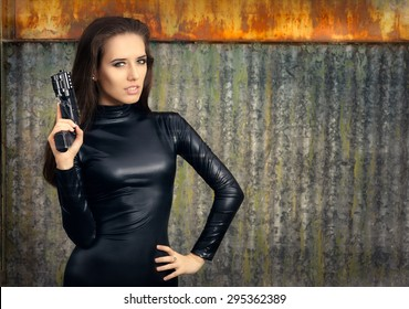 Spy Agent Woman in Black Leather Suit Holding Gun - Portrait of a super heroine in action