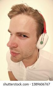 Spy concept. Man listening headphones suspiciously as spy. Guy with earphones listens sound. Man suspicious listening headphones white background close up. Secret spy eavesdrops. Spy use technology.