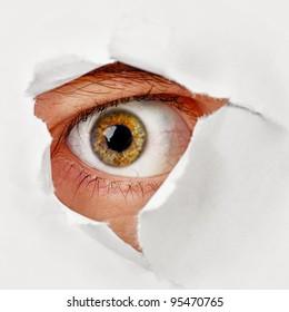 Spy eye peeking through a hole in the paper
