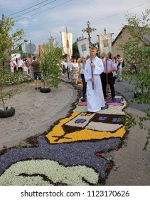 Spycimierz / Poland - 31 May 2018: Ceremonial procession of Corpus Christi holiday in Poland catholic priestes and believers holds cross and walk on amazing artistic natural carpets made of flowers