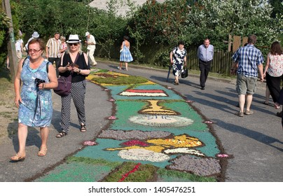Spycimierz / Poland - May 31 2018: Traditional floral carpets on ground in Spycimierz, Poland, makes by local people to celebrate Corpus Christi holiday, tourists walk along it and watch.