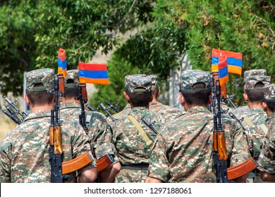 A squad of Armenian soldiers marching with automatic guns and Armenian flags attached to the bayonet knives. Back view with green trees on blurred background, Armenia