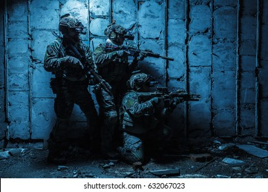Squad of Army Rangers with rifle and machine gun moving along the concrete wall of ruined destroyed building on mission. They are ready to start firing if enemy appear. Outdoor location shot, darkness