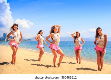 squad of cheerleaders in white pink uniform stands on sand beach holds hands on hip against sea wind shakes long hair