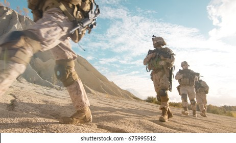 Squad of Fully Equipped and Armed Soldiers Moving in Single File in the Desert.