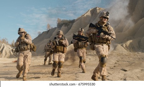 Squad of Fully Equipped, Armed Soldiers Running and Attacking During Military Operation in the Desert.